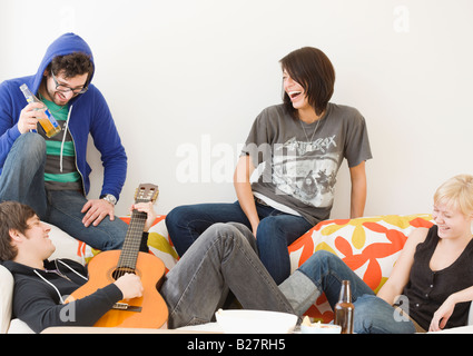 Groupe d'amis relaxing on sofa Banque D'Images