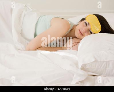 Woman laying in bed avec un masque pour les yeux Banque D'Images