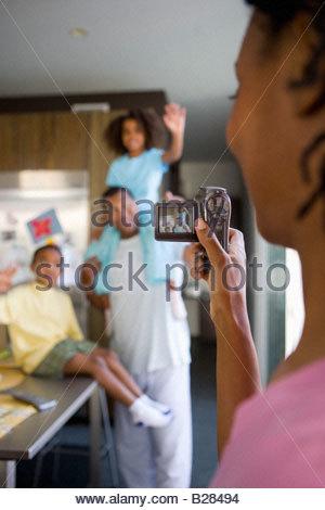 Mère de famille d'enregistrement dans la cuisine avec caméscope Banque D'Images