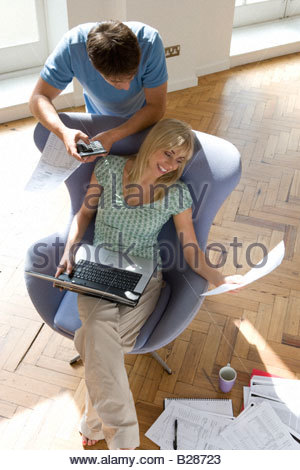 Man woman with laptop computer in armchair Banque D'Images