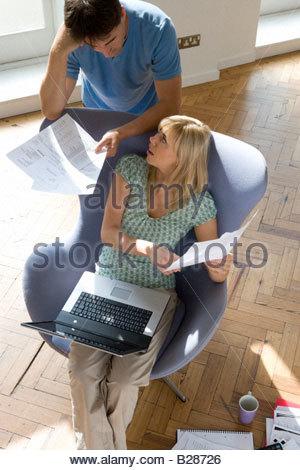 Couple avec la paperasse, woman with laptop computer in armchair Banque D'Images