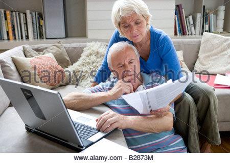 Couple avec un ordinateur portable et de documents dans la salle de séjour Banque D'Images