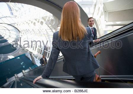 Les gens d'affaires à l'aide d'escalators in airport Banque D'Images