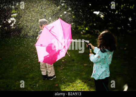 Garçon âgé de 6 ans se cache derrière un parapluie rose Banque D'Images