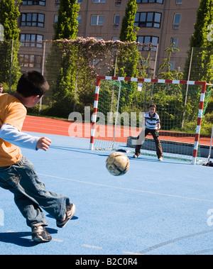 Les enfants jouent au football sur un terrain de football à Berlin-Mitte, Berlin, Germany, Europe