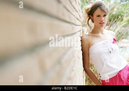 Jeune femme élégante leaning against wall. Banque D'Images