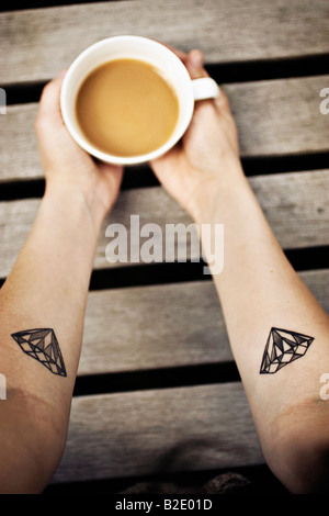 Gros plan d'une main de femme tenant une tasse de café