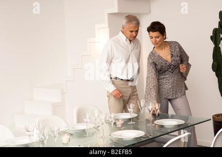 Mid adult woman définition d'une table à manger et un homme debout à côté d'elle Banque D'Images
