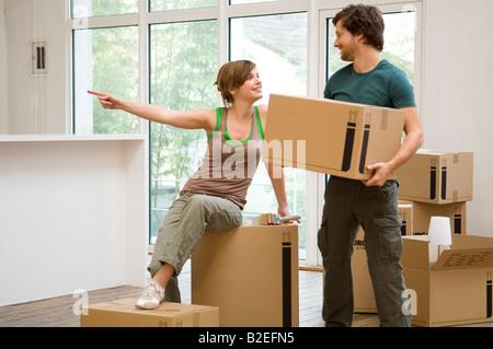 Mid adult man holding une boîte en carton et une jeune femme en pointant à l'écart