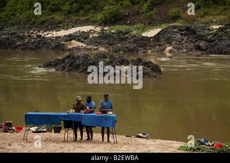 Assistants pour le rafting expedition de déjeuner sur les berges du Zambèze. Banque D'Images