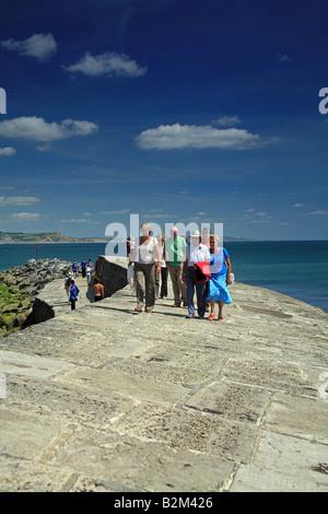 Les visiteurs à marcher le long de la Cobb à Lyme Regis, dans le Dorset, UK Banque D'Images