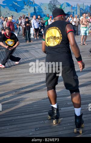 Un homme danse sur patins à roulettes sur le Boardwalk Coney Island à Brooklyn, NY