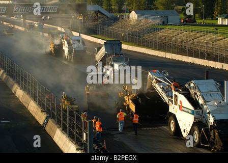 Des machines d'asphalte pour pavage travaillant dans la formation d'echelon pendant la reconstruction de la piste Banque D'Images