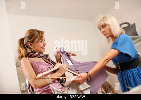 Les jeunes femmes à la recherche de vêtements en boutique Banque D'Images