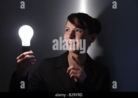 Businesswoman âgés de 24 avec une ampoule dans la main Banque D'Images