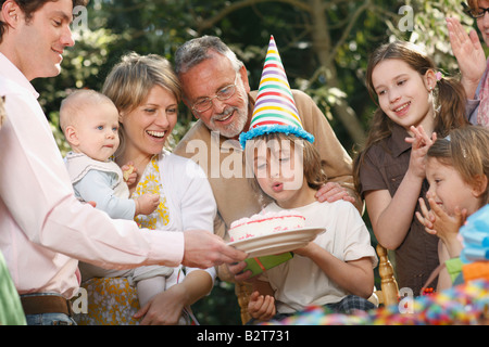 Young boy blowing out candles at party Banque D'Images
