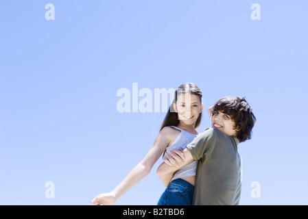 Teenage boy picking up petite sœur, s'étreindre, low angle view Banque D'Images