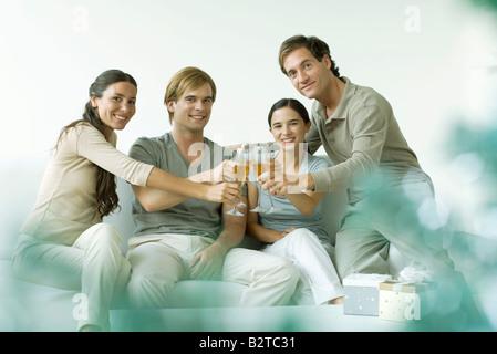 Amis adultes tintement des verres de champagne, smiling at camera Banque D'Images