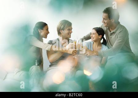 Amis adultes tintement des verres de champagne, smiling Banque D'Images