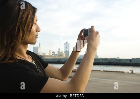Young man photographing waterfront avec appareil photo numérique, side view Banque D'Images