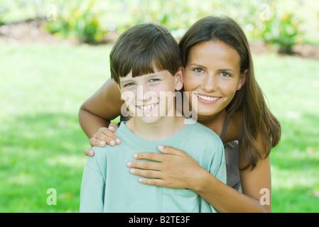 Teen girl debout derrière son jeune frère, les mains sur l'épaule et le coeur, les deux smiling at camera