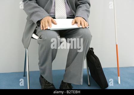 Businessman sitting in chair, soutenu de la canne blanche à côté de lui, tenant le document, cropped