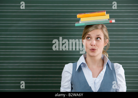 Enseignant avec des livres sur la tête. Banque D'Images