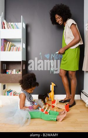 Une mère regardant sa fille jouer Banque D'Images