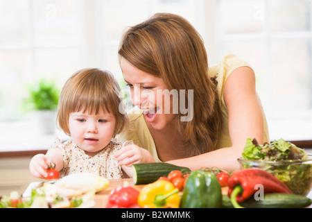 Mère et fille en cuisine faire une salade smiling Banque D'Images