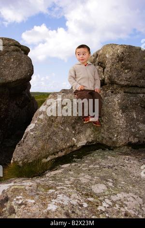 Petit garçon effronté avec expression drole assis sur le granit tor dans le Dartmoor National Park Banque D'Images