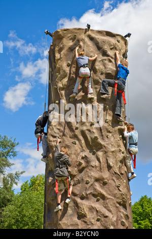 Les jeunes enfants s'amusant de grimper une tour d'escalade Banque D'Images
