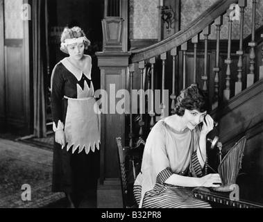 Maid à l'écoute de l'appel téléphonique de womans Banque D'Images