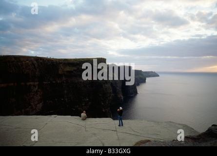 Un couple prend dans la vue depuis les falaises de Moher sur la côte irlandaise. Banque D'Images