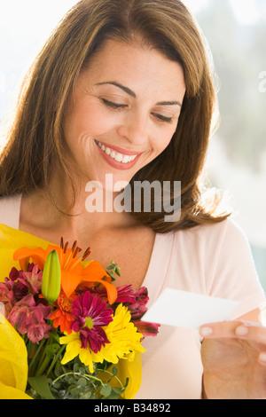 Femme tenant des fleurs et lecture remarque smiling Banque D'Images