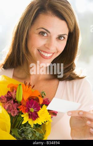 Femme tenant des fleurs et remarque smiling Banque D'Images