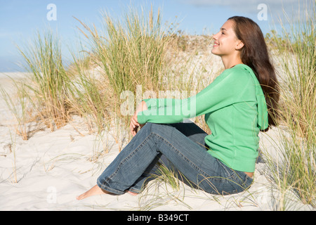 Jeune femme posant sur une colline de sable