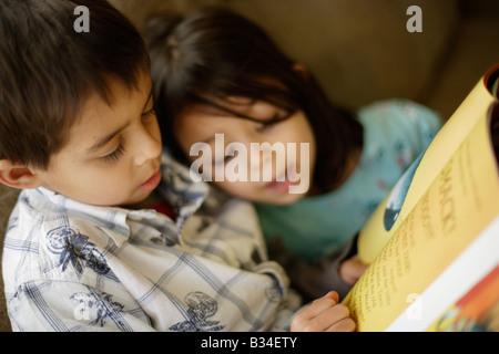 Garçon de 6 ans lit une histoire à sa petite sœur de 5 ans Banque D'Images