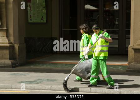 Espagne Barcelone deux femmes dans des uniformes verts et des gilets de sécurité un balai pour nettoyer le trottoir Banque D'Images