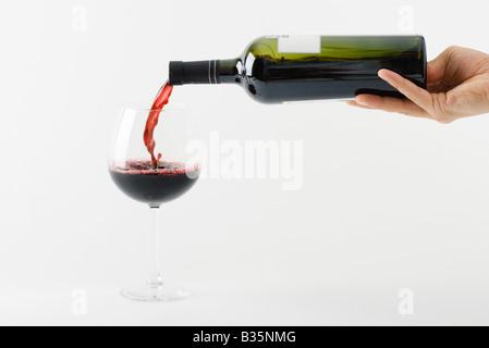 Verser le vin rouge à la main dans du verre Banque D'Images