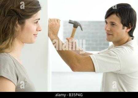 Germany, man hammering nail into wall Banque D'Images
