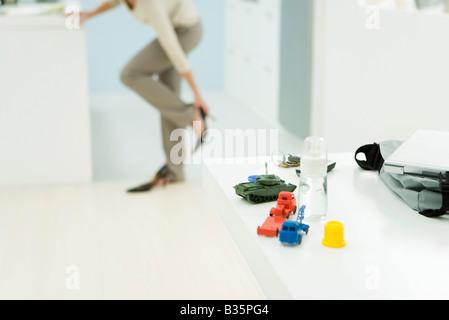 Femme professionnelle s'habiller, se concentrer sur bouteille de bébé et des jouets en premier plan Banque D'Images