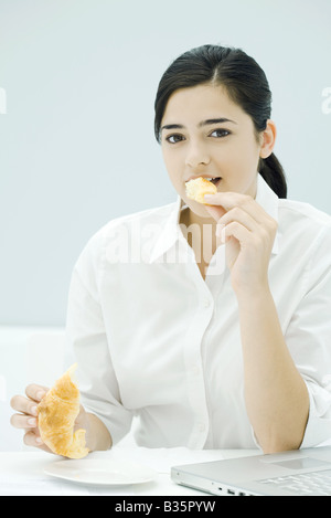 Young woman eating croissant, sitting at desk, looking at camera Banque D'Images