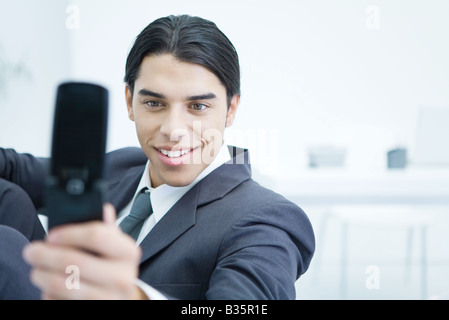 Young businessman using cell phone pour prendre une photo de lui-même, smiling Banque D'Images