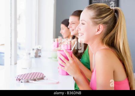 Trois jeunes femmes ayant une boisson froide dans une cafétéria Banque D'Images