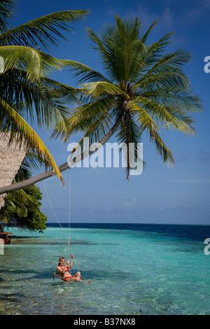 Fille se balançant sur rope swing sur South Ari Atoll Maldives près de l'Inde Banque D'Images