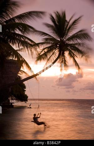 Fille se balançant sur rope swing au coucher du soleil sur le Sud de l'Atoll d'Ari aux Maldives, près de l'Inde Banque D'Images