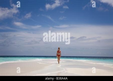 Jeune femme marchant le long de la plage de sable blanc déserte entourée par les eaux tropicales près de l'Inde Banque D'Images