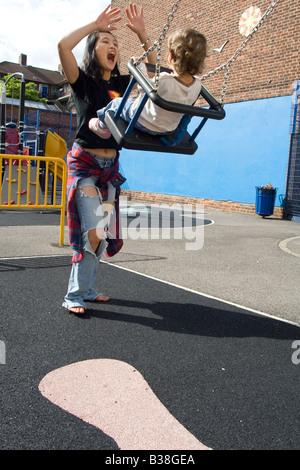 Exhuberent asiatique coréen mère jouant avec un bébé de l'année dans une aire sur l'immobilier conseil à Hoxton Banque D'Images