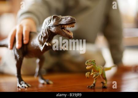 Tyrannosaurus rex modèle dans les mains de six ans de manger un autre jouet d'un dinosaure Velociraptor Banque D'Images