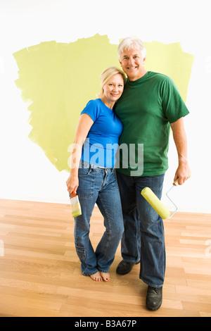 Couple d'âge moyen en face de wall ils sont vert peinture Banque D'Images